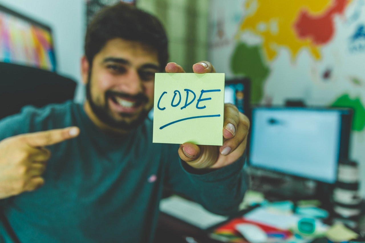 man holding a paper with code text