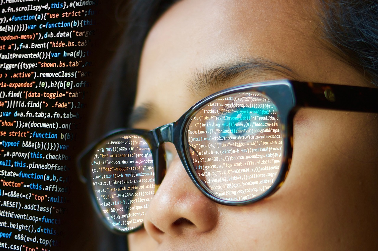 woman wearing glasses with programming codes