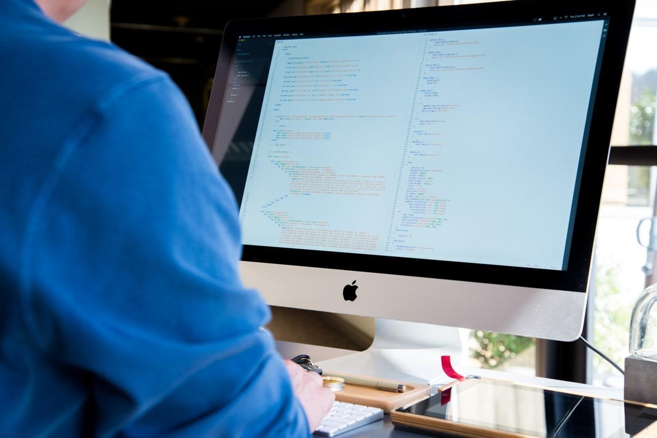 Person coding on mac